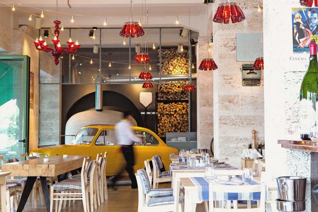 Sala restaurantului Bocca Lupo din Bucuresti, cu mese si scaune si un Fiat galben