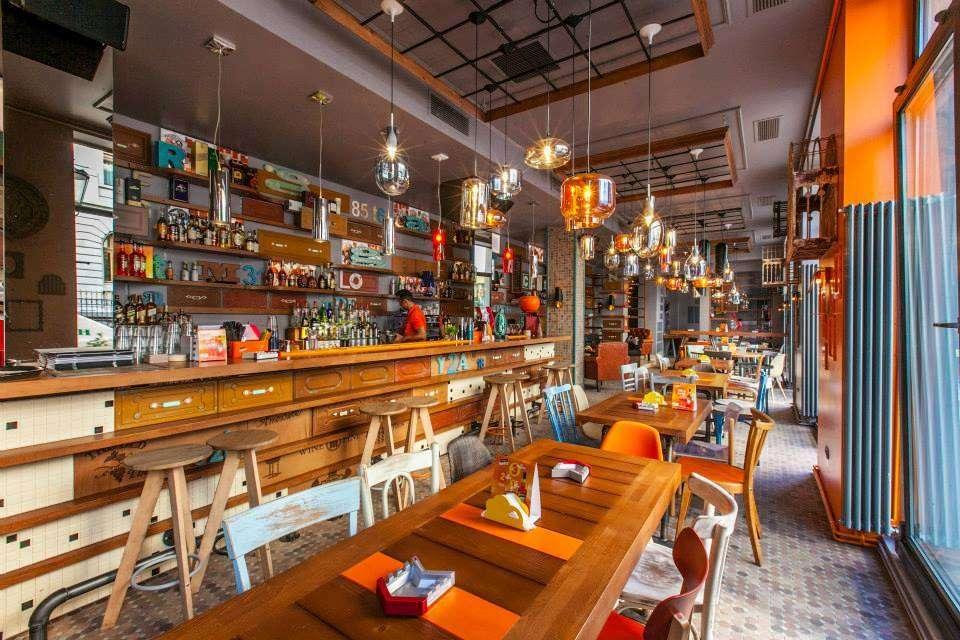 Restaurant Entourage Centrul Vechi, cu mese din lemn, bar si lampi suspendate