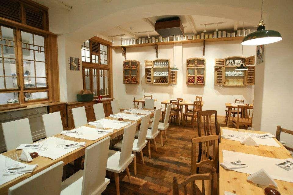 Sala restaurantului Lacrimi si Sfinti, cu mese lungi si scaune din lemn