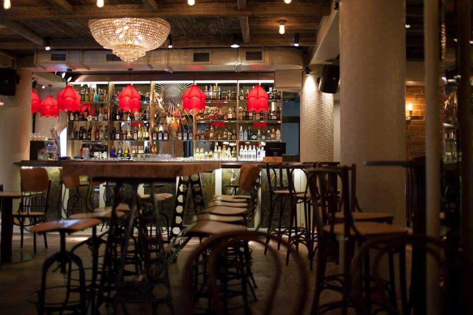 Salon Golescu, un restaurant bucurestean cu mese bar, scaune din lemn si lampi rosii la bar